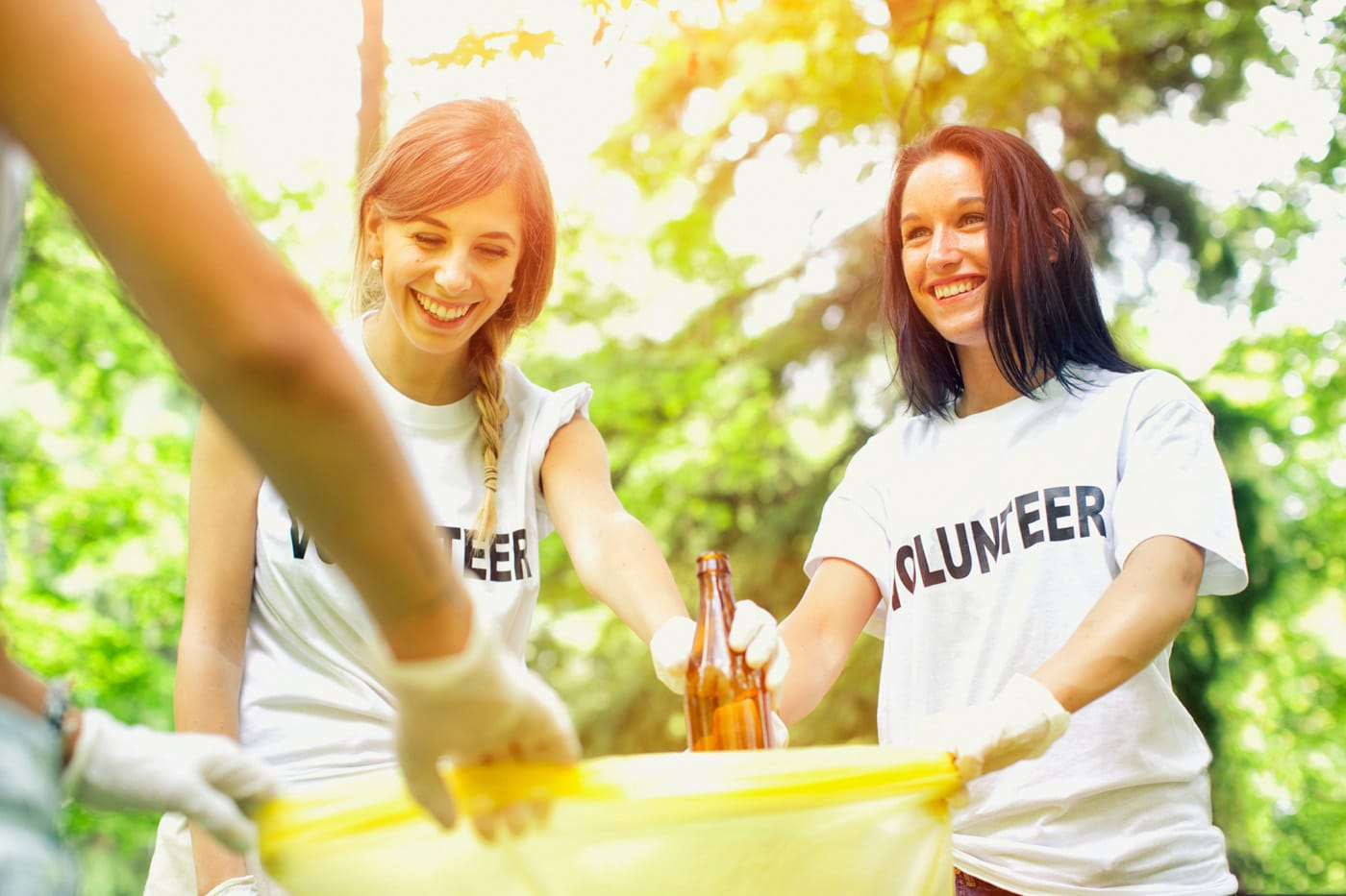 Stock photo of two volunteers putting a glass bottle in a trashbag