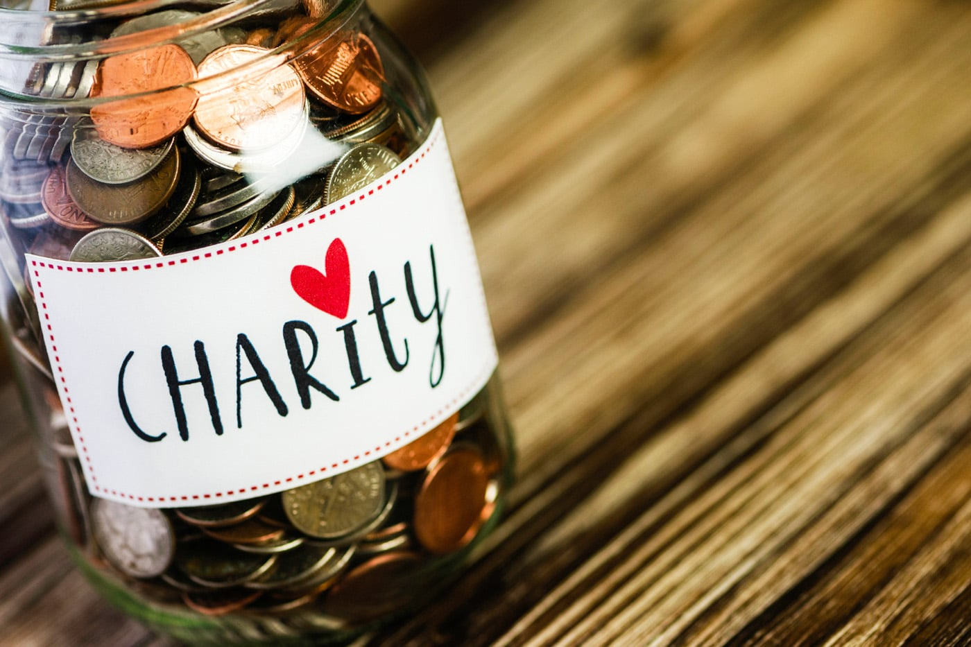 Stock photo of a jar filled with change that is labeled charity