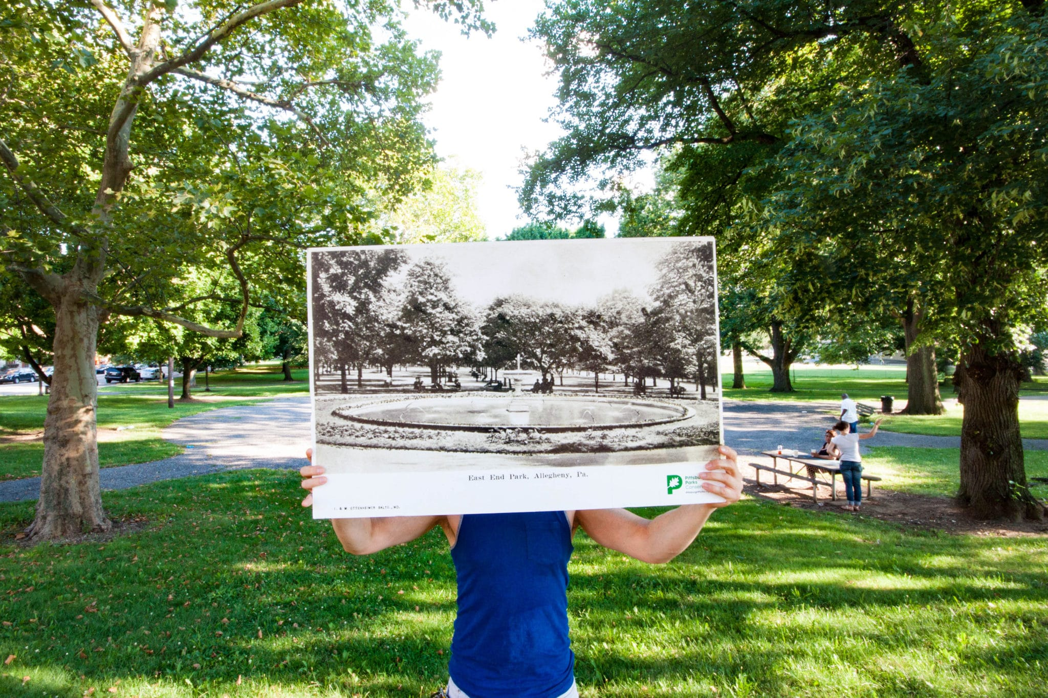 An image of a park-goer holding a historical photograph of Allegheny Commons.