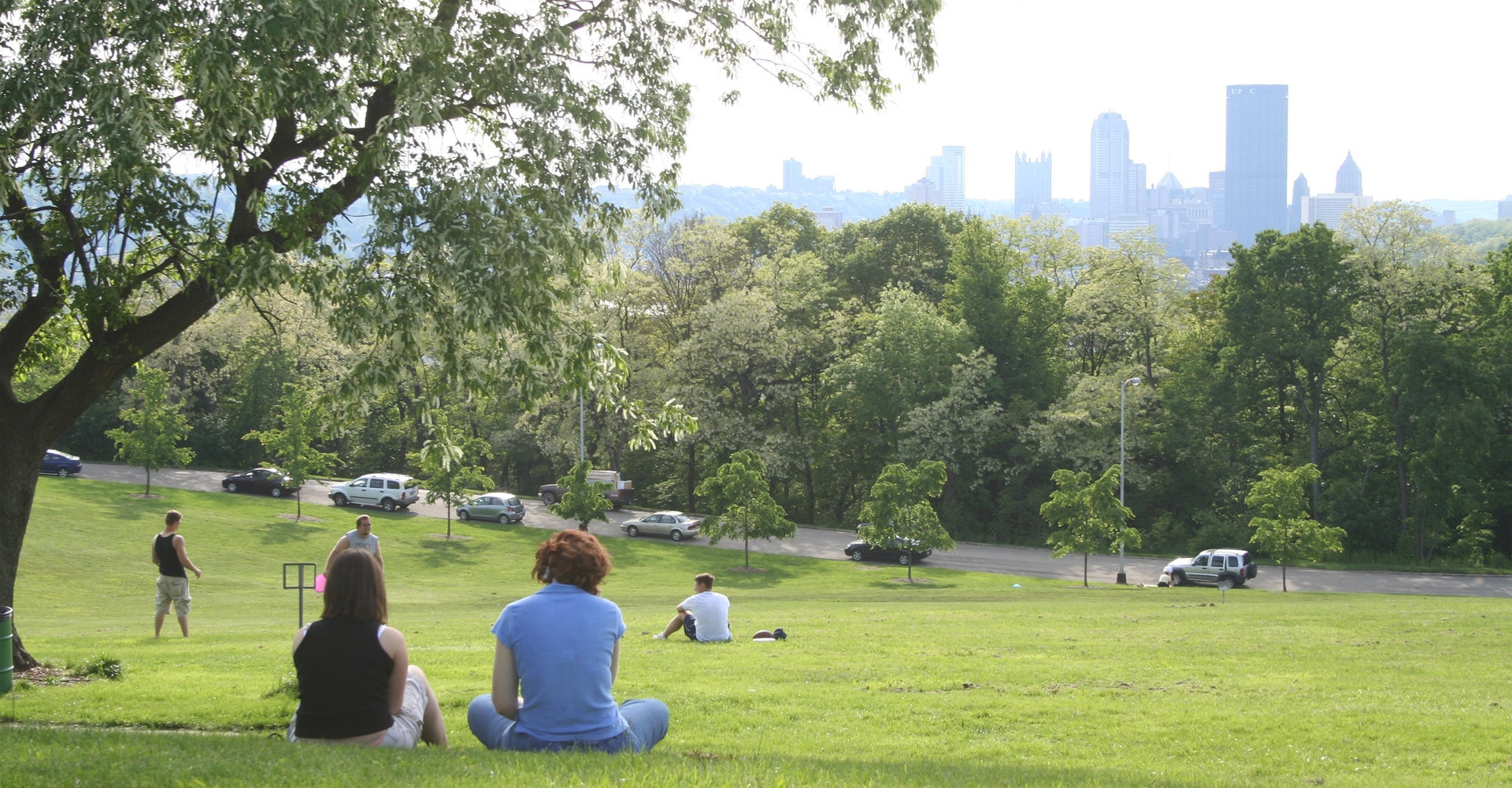 People sitting in a field in Schenley Park with the city skyline in the distance