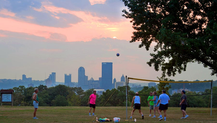 A group of people playing volleyball in the Park at sunset with the city skyline behind them