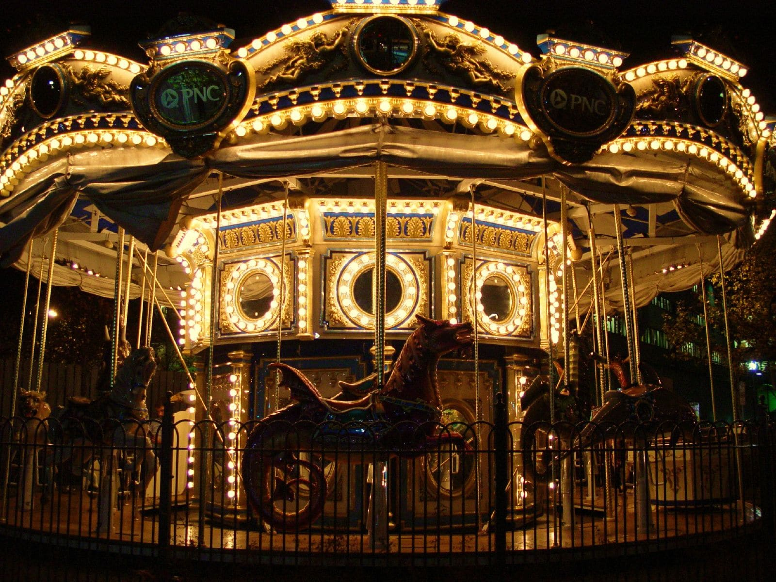 The carousel lit up at night in Schenley Plaza