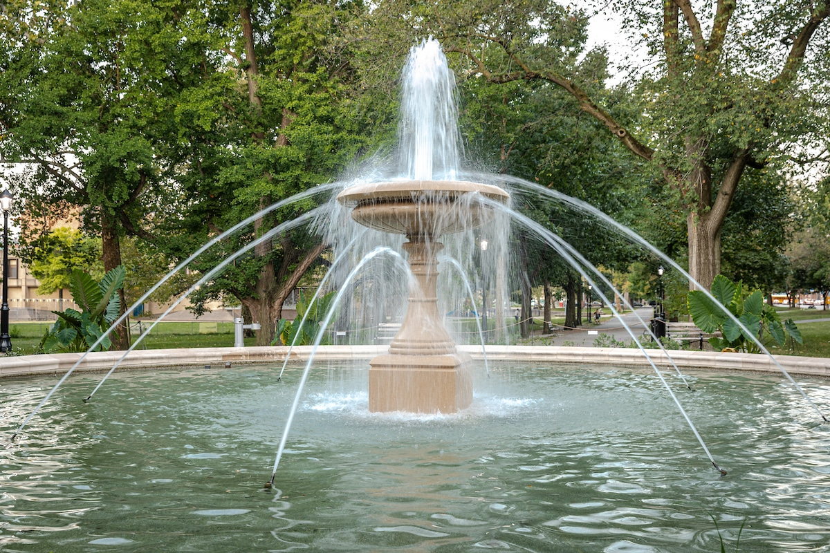 An image of the fountain in Allegheny Commons Park surrounded by trees and benches