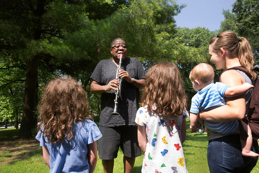 A group watching a man play the clarinet