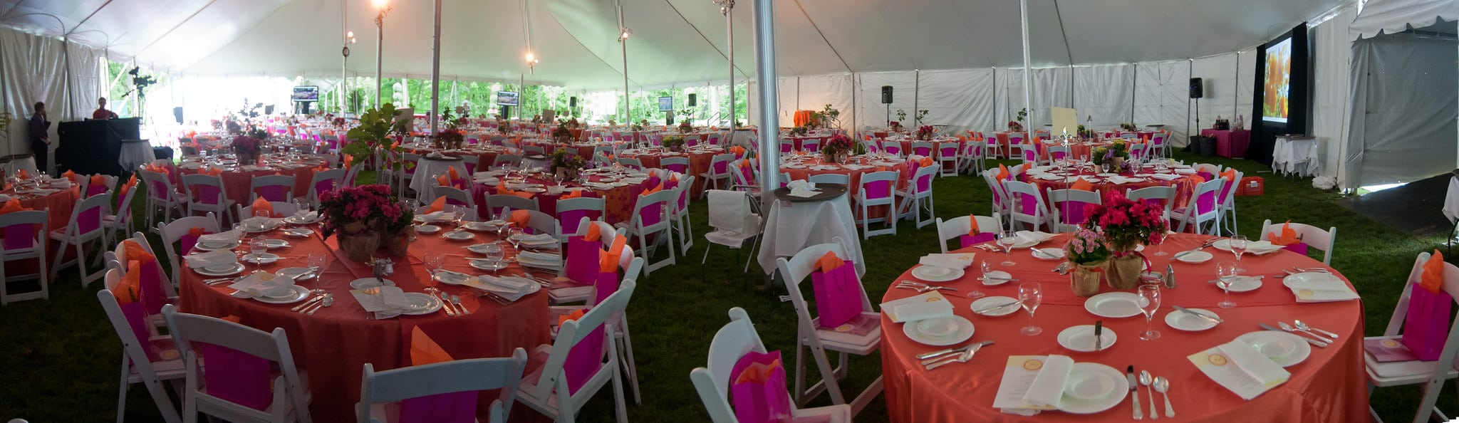 Event with set tables and chairs under a tent