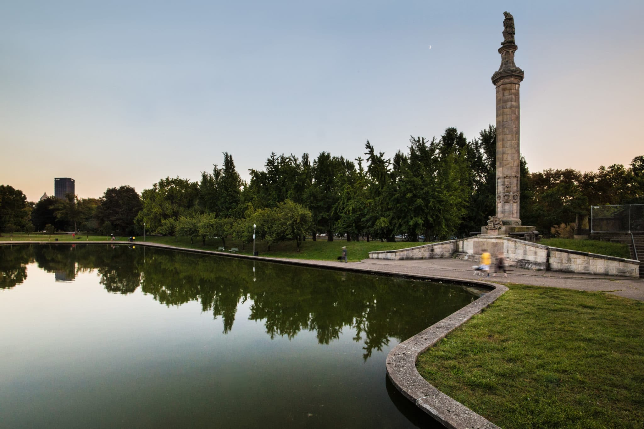 An image of Allegheny Commons Lake Elizabeth including a tall statue at sunset.