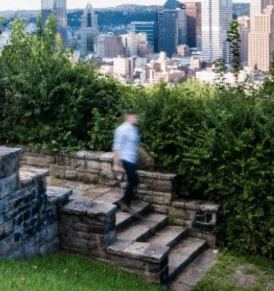 Person walking down steps at Emerald View Park with view of Pittsburgh skyline