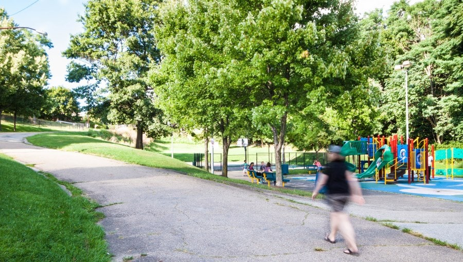 Person walking by Olympia Park Playground
