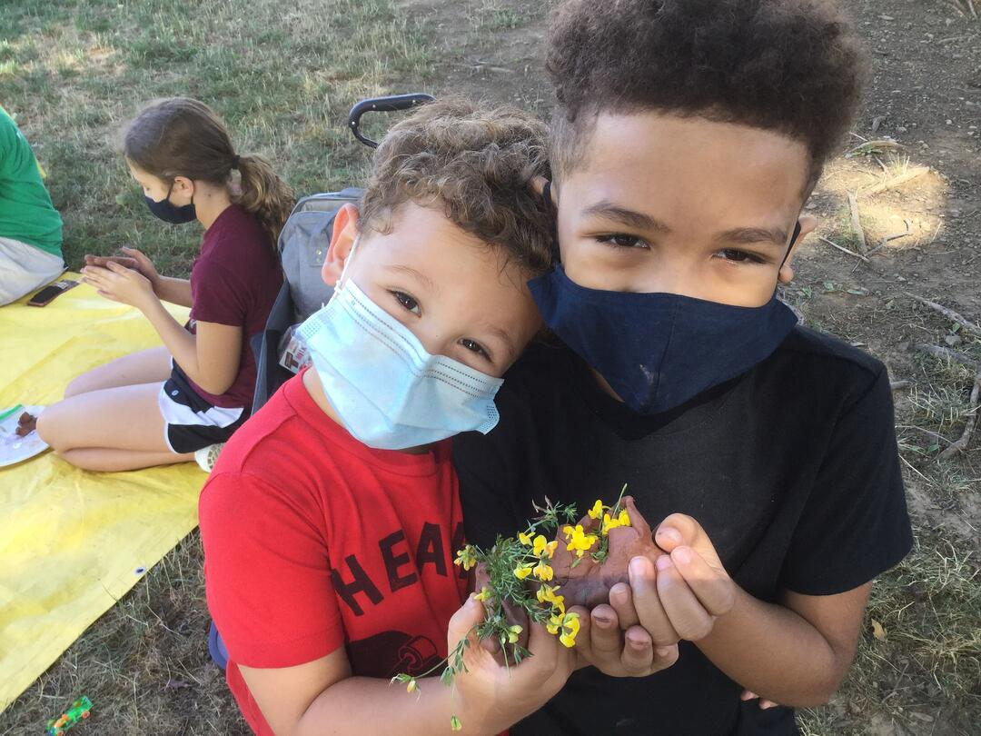 Two children standing together wearing masks and holding yellow flowers