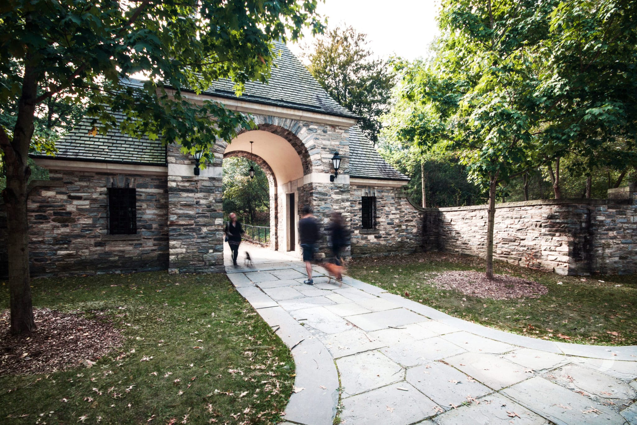 Stone gatehouse to Frick Park with people walking through it