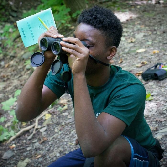 Teen boy looking through binoculars