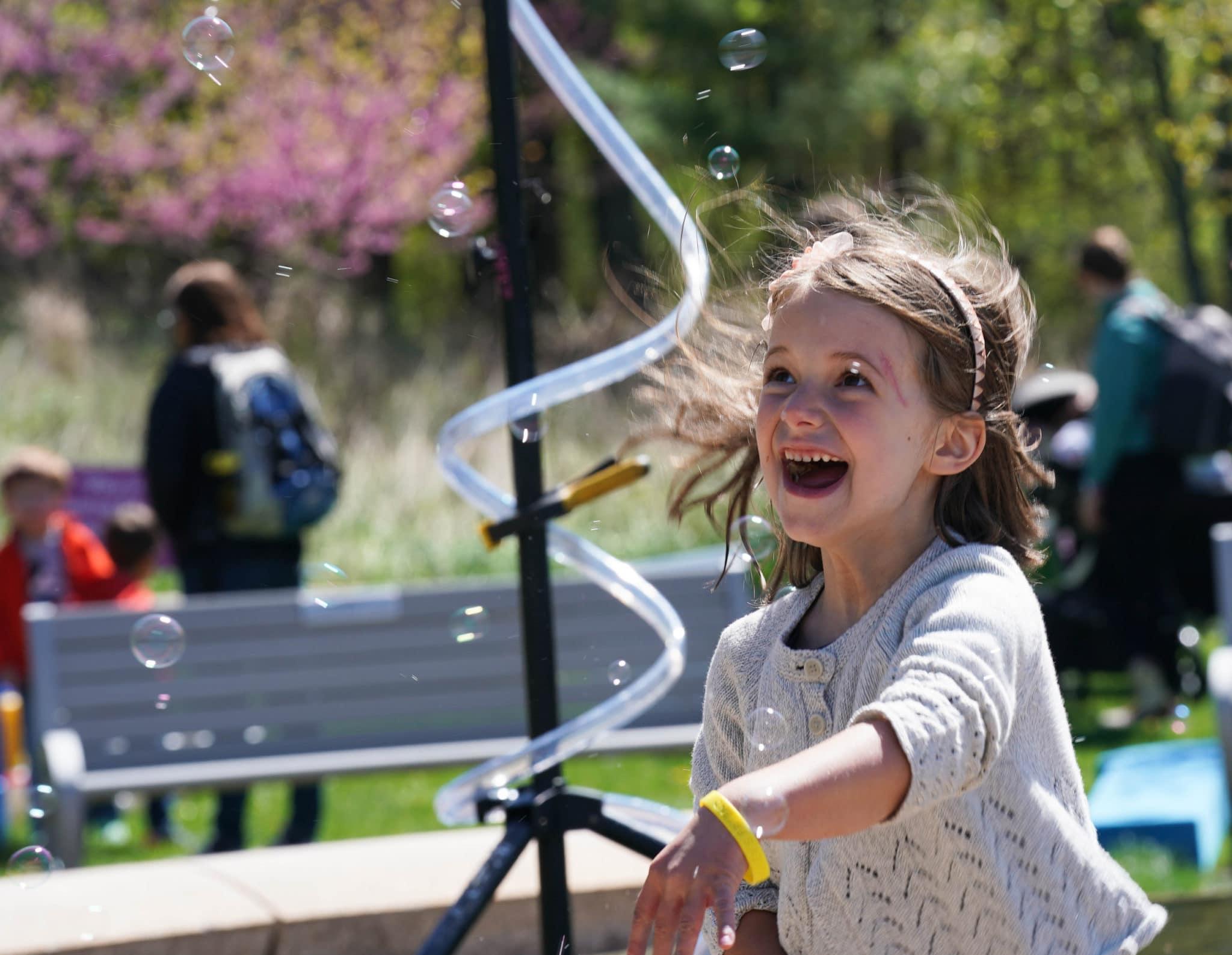 A young girl running through bubbles