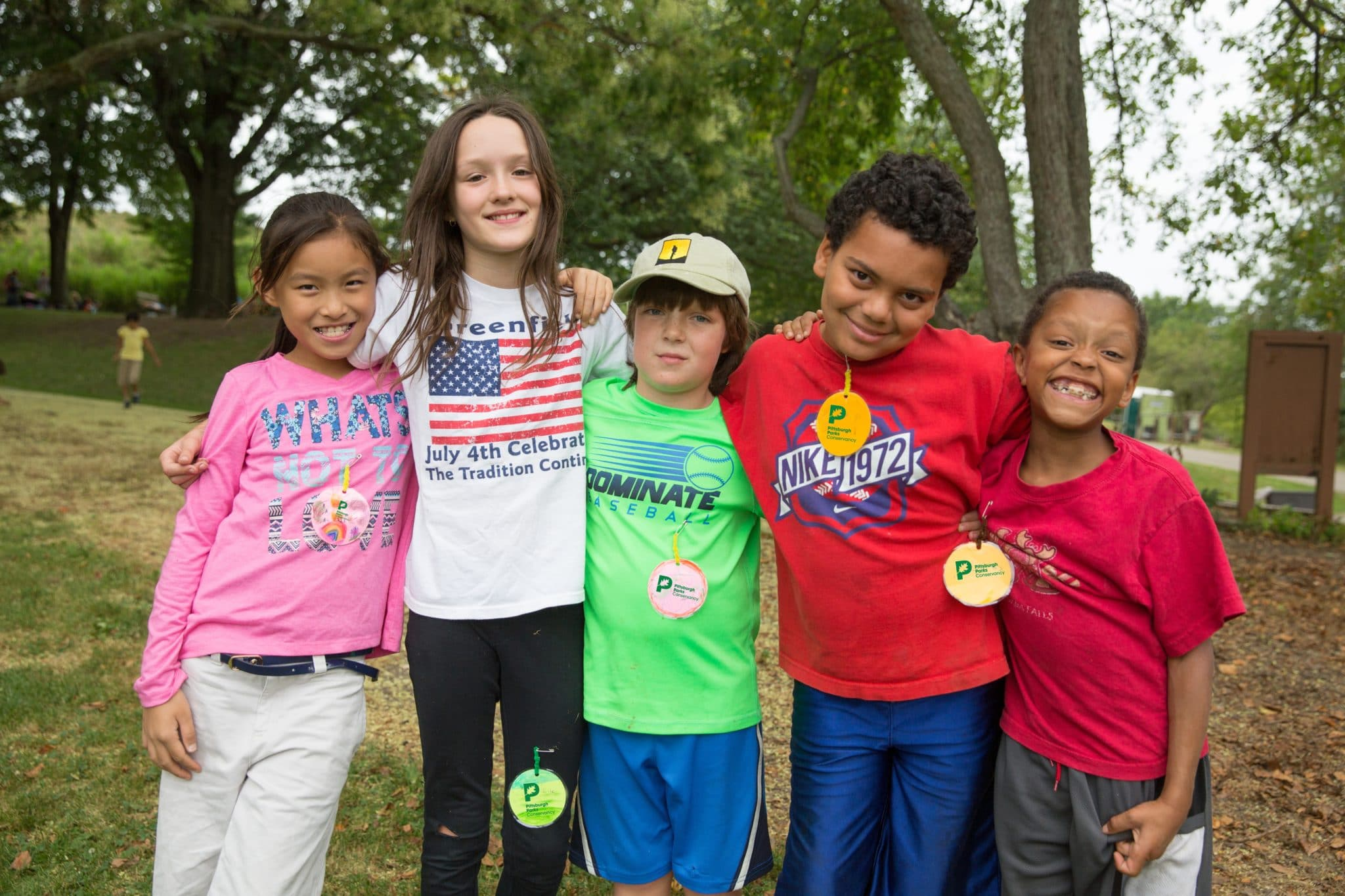 Summer Camp Education Program 2015 Mark Simpson Diverse Ethnic Line Kids Smile Outside Trees Pink Green Red H