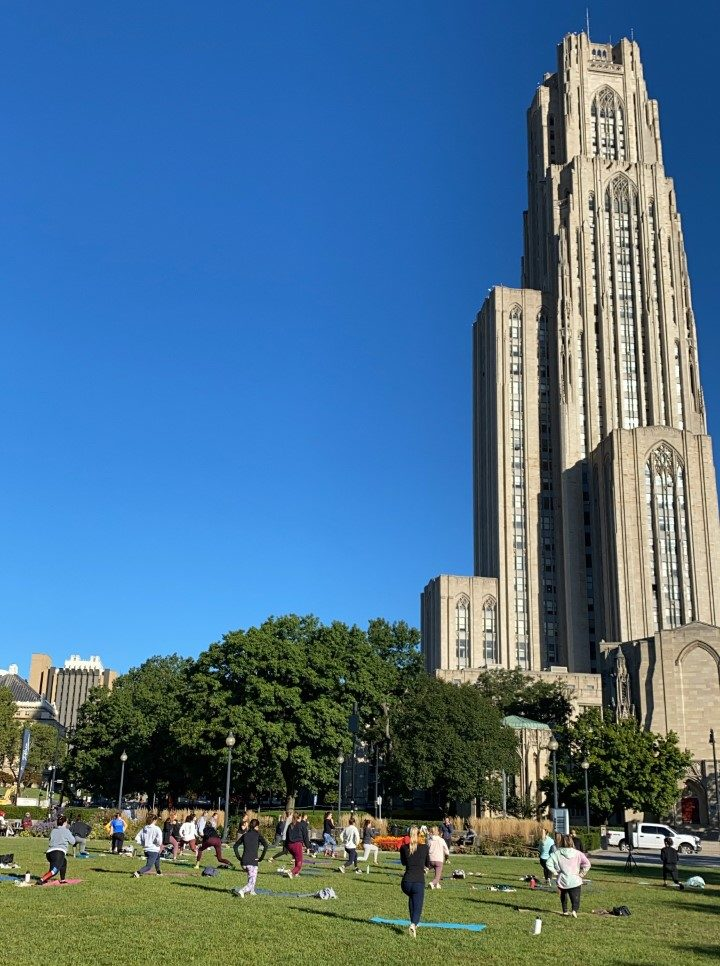 Image of people doing yoga in Schenley Park in front of the Cathedral of Learning