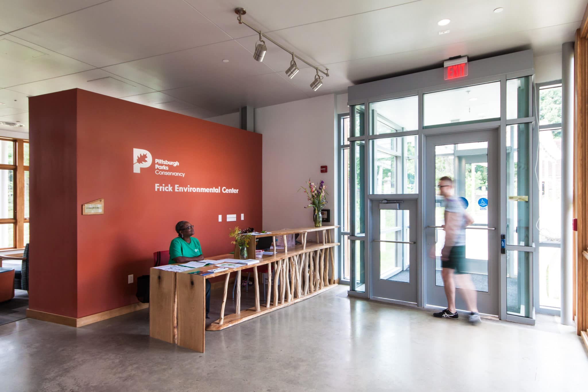 Staff member and park visitor interacting at the FEC entryway