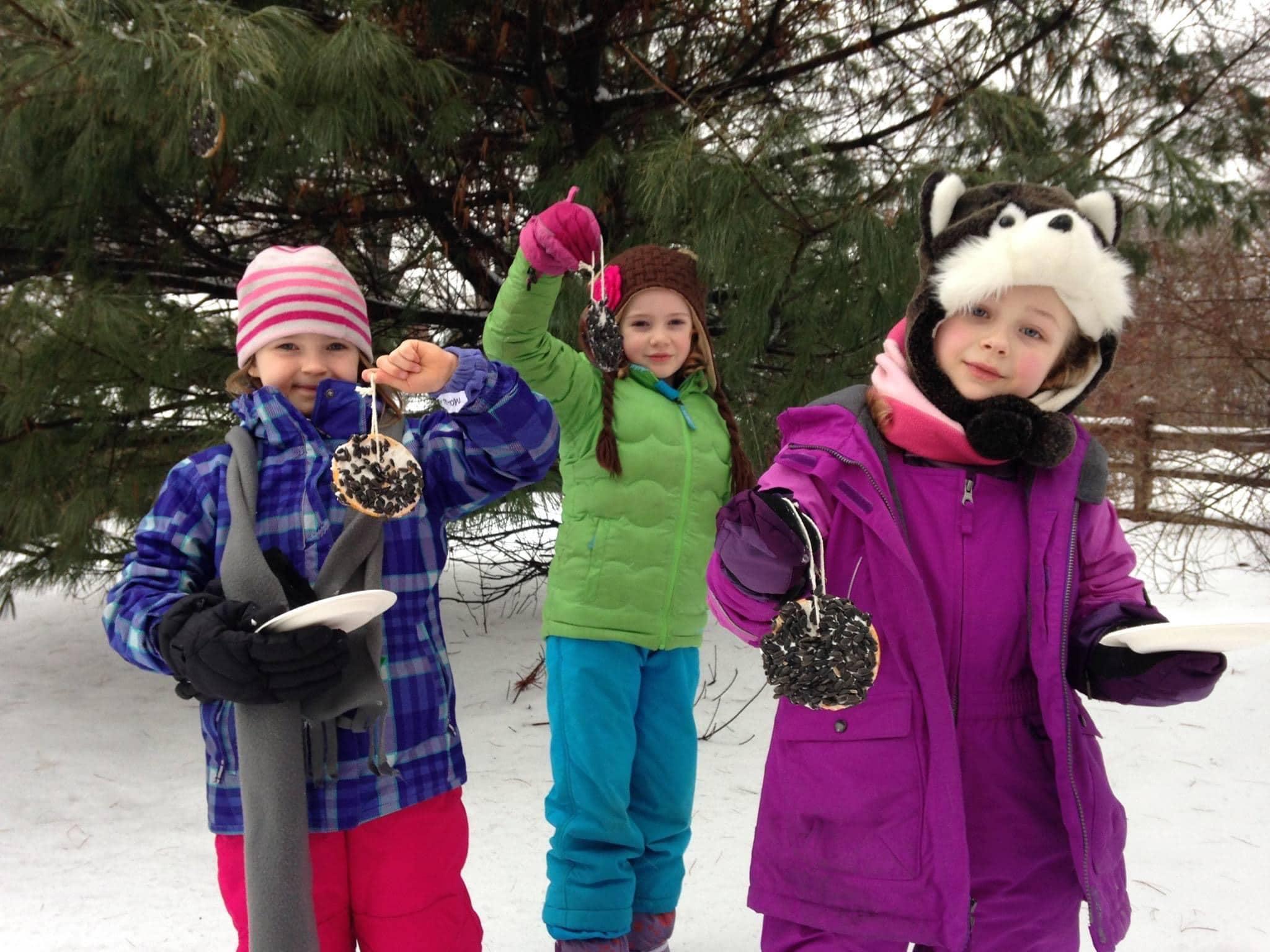 Three children holding bird feeders in the snow