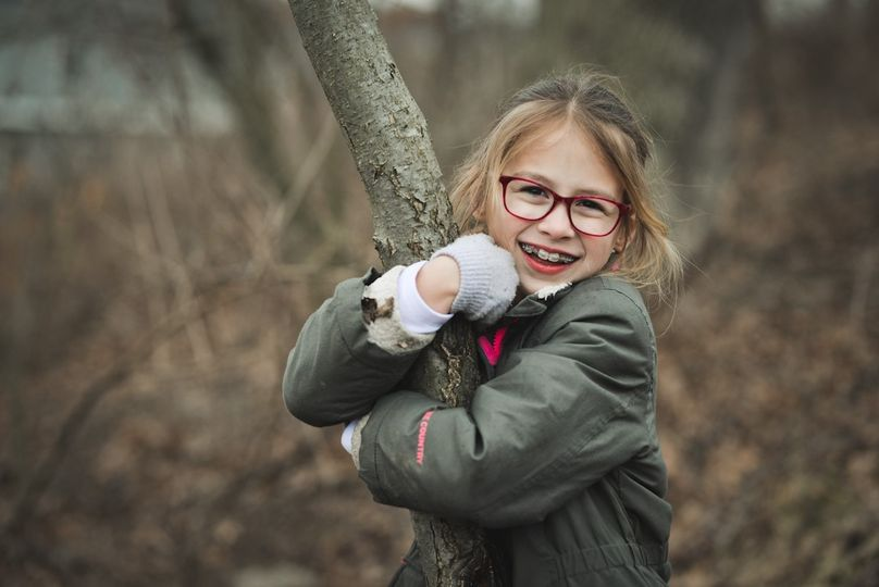 A young girl holding onto a branch