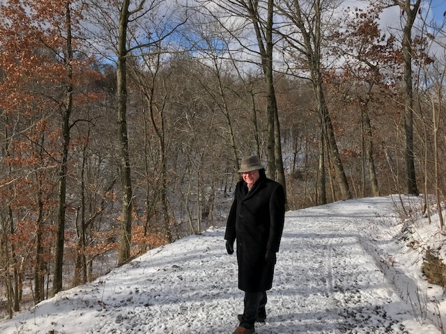 A man walking in the snow in Frick Park.