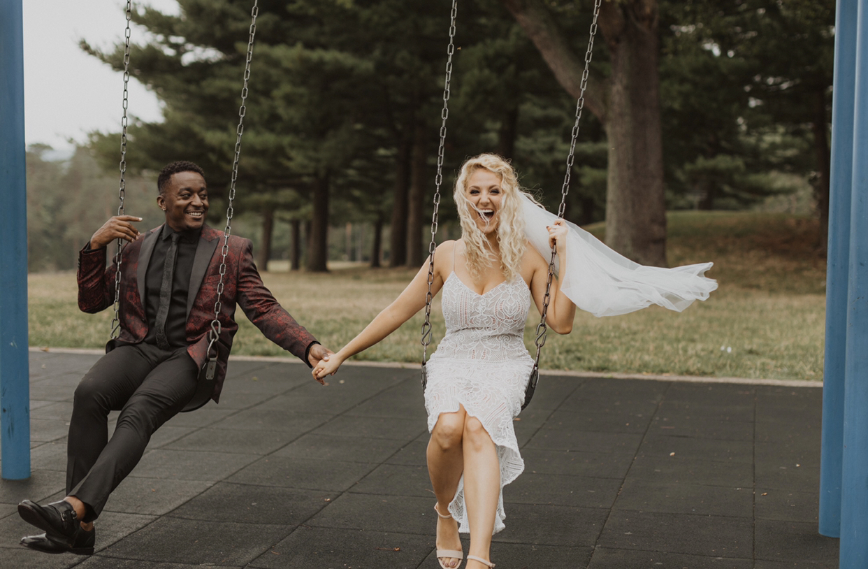 Michelle and Jansen Jones on their wedding day in Schenley Park playing on a swing set.