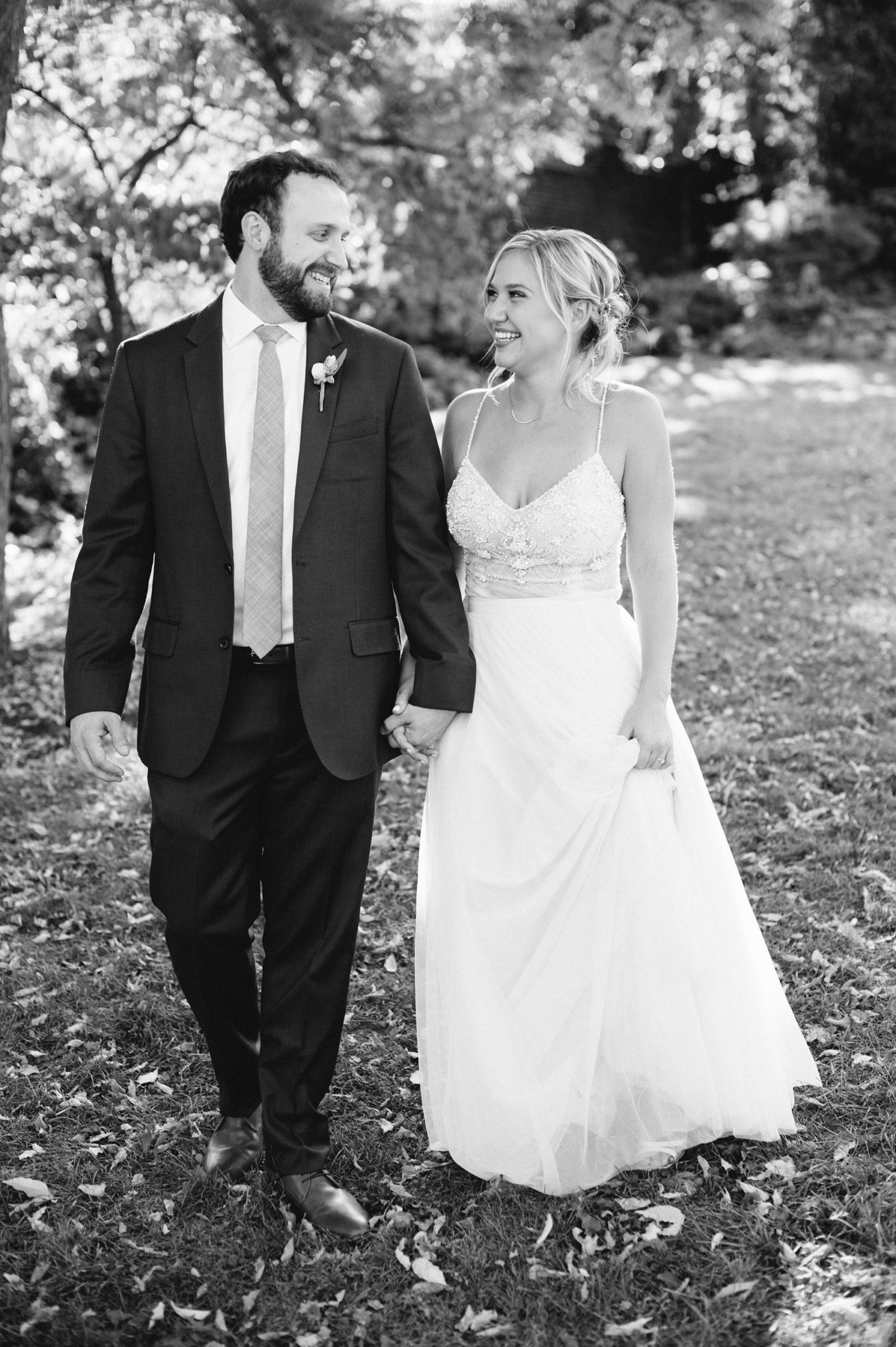 A black and white photo of a couple on their wedding day walking in Mellon Park