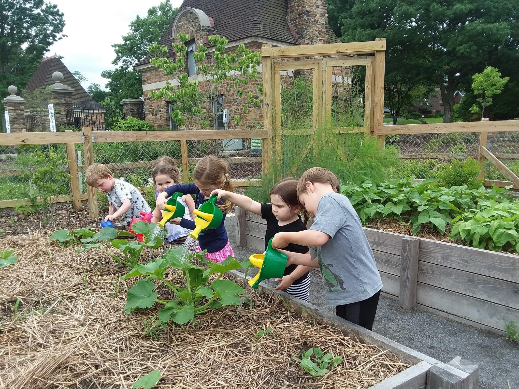 Children watering plants in the From Slavery to Freedom garden