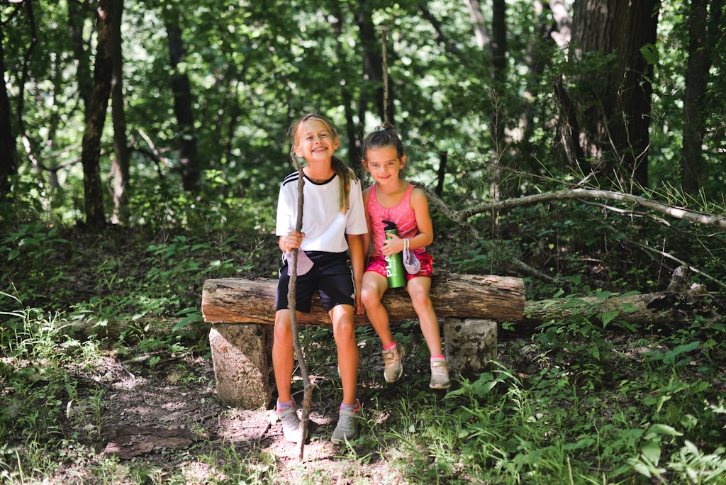 Two children sitting on a log