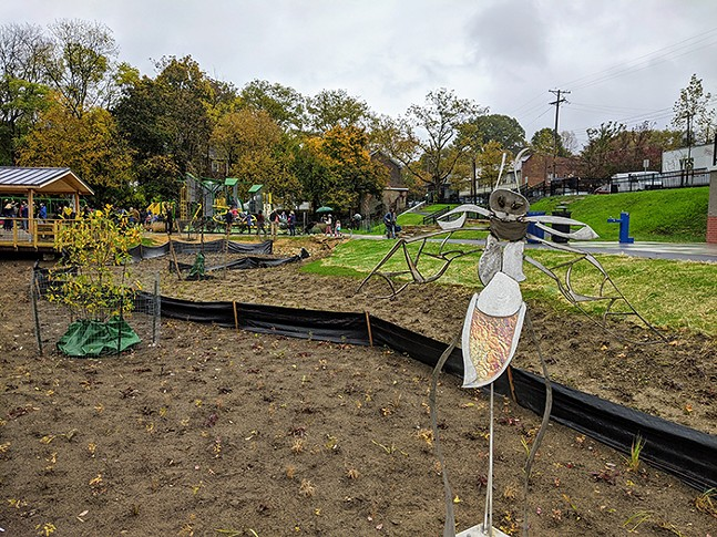 Large decorative bug in a dirt area with plants and a park in the background
