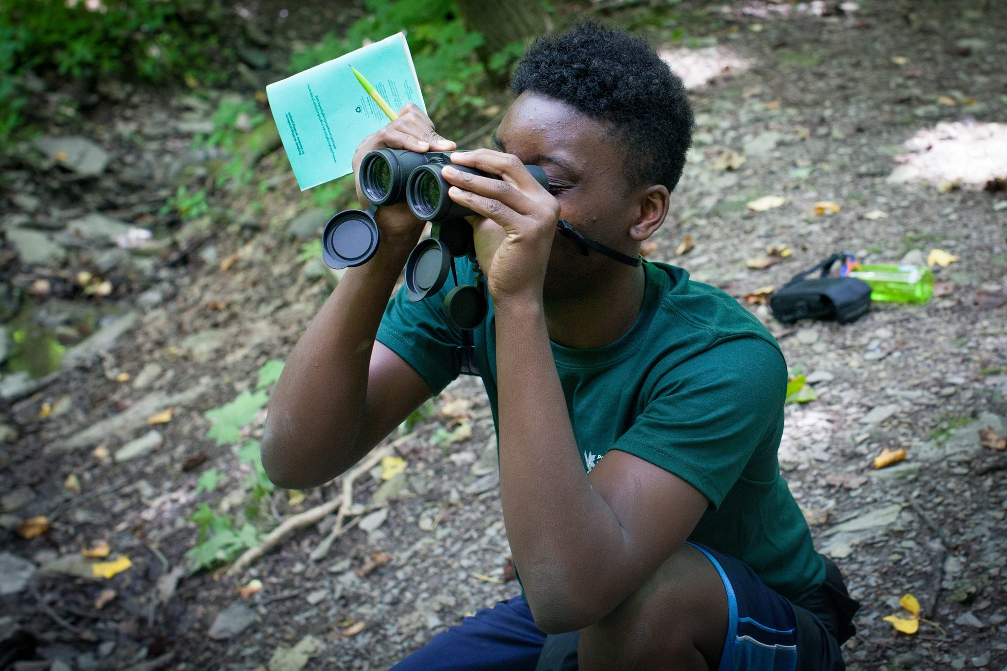 A young person looking through binoculars