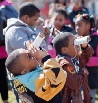 A group of kids looking into binoculars.