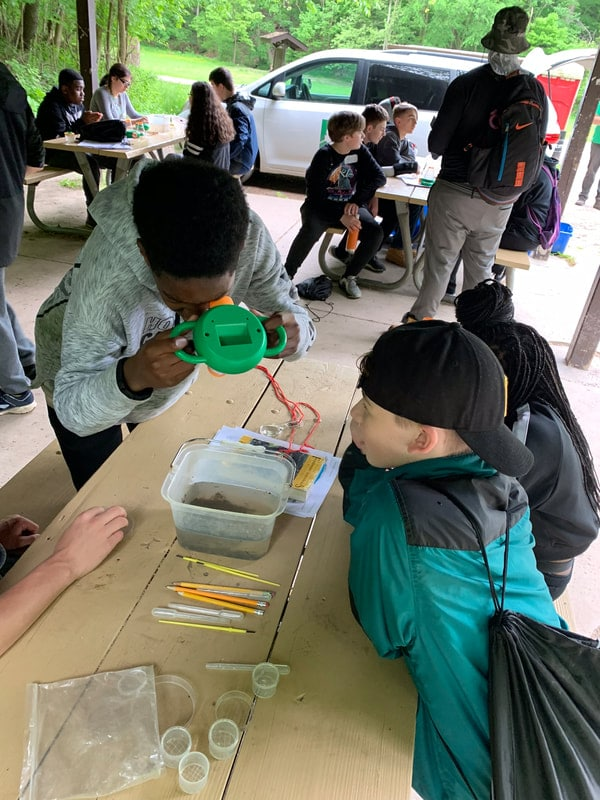 Students looking through magnifiers