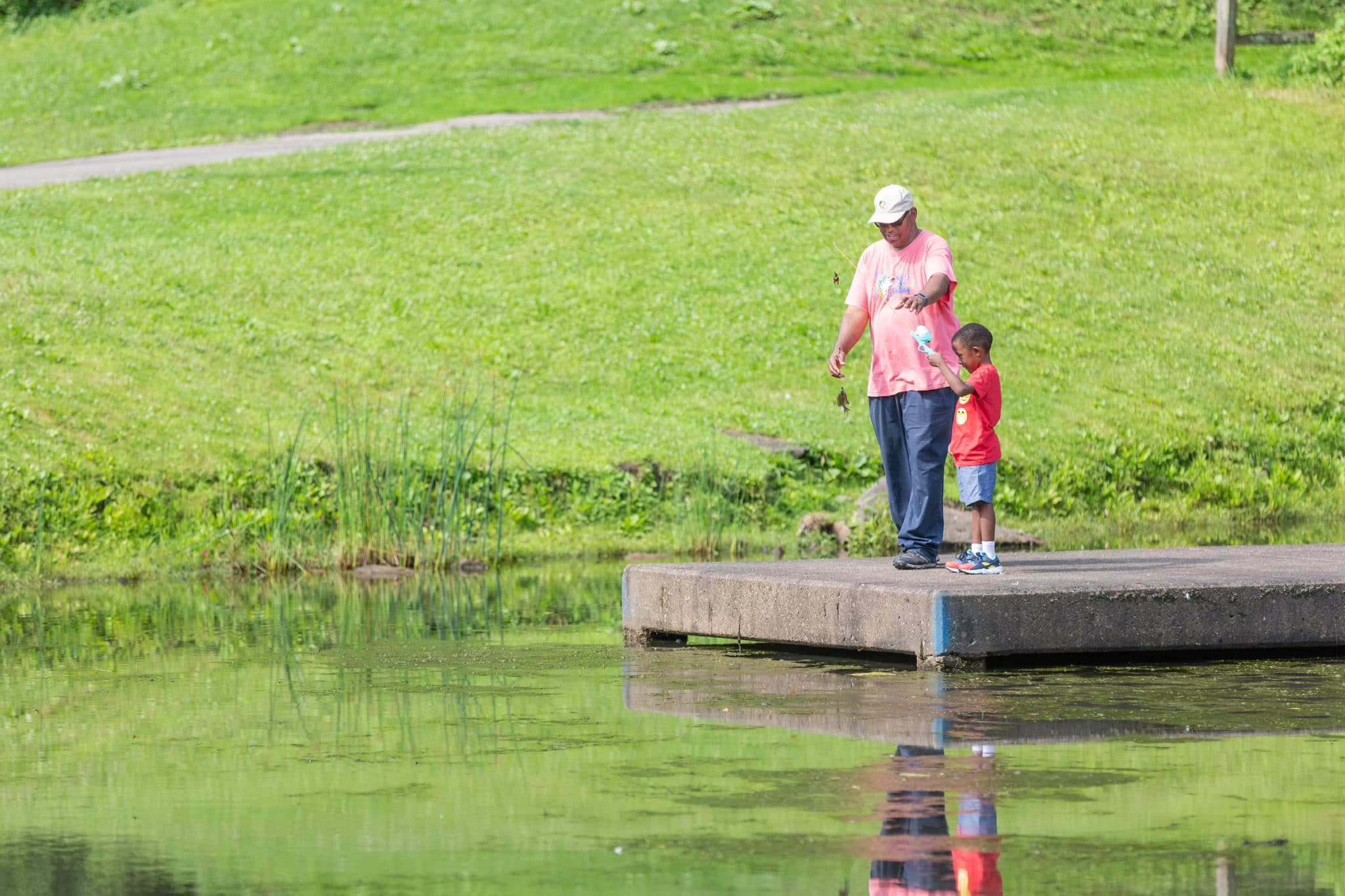Adult and child fishing in a lake