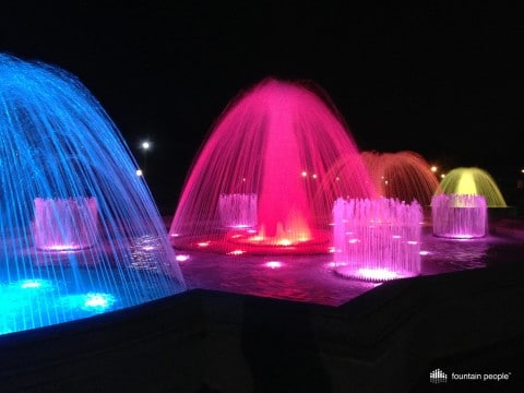Water fountains at night, lit from the bottom with colorful lighting