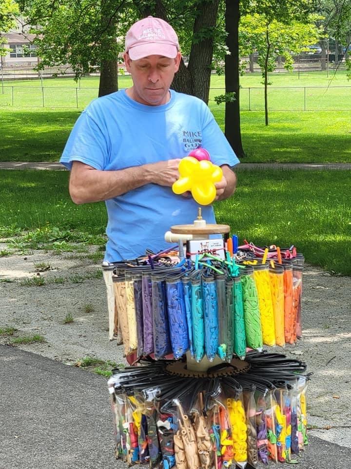 Balloon artist holding a yellow balloon