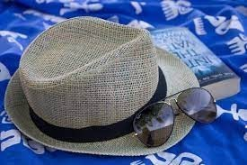 Hat and sunglasses on a picnic blanket