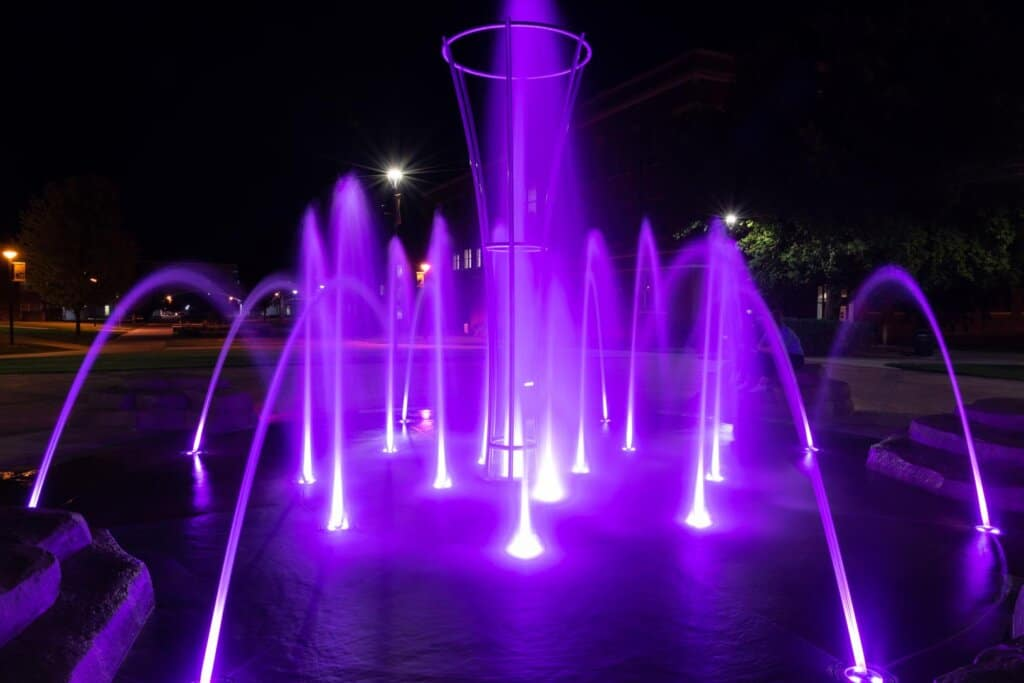 Water fountains at night, lit from the bottom with purple lighting