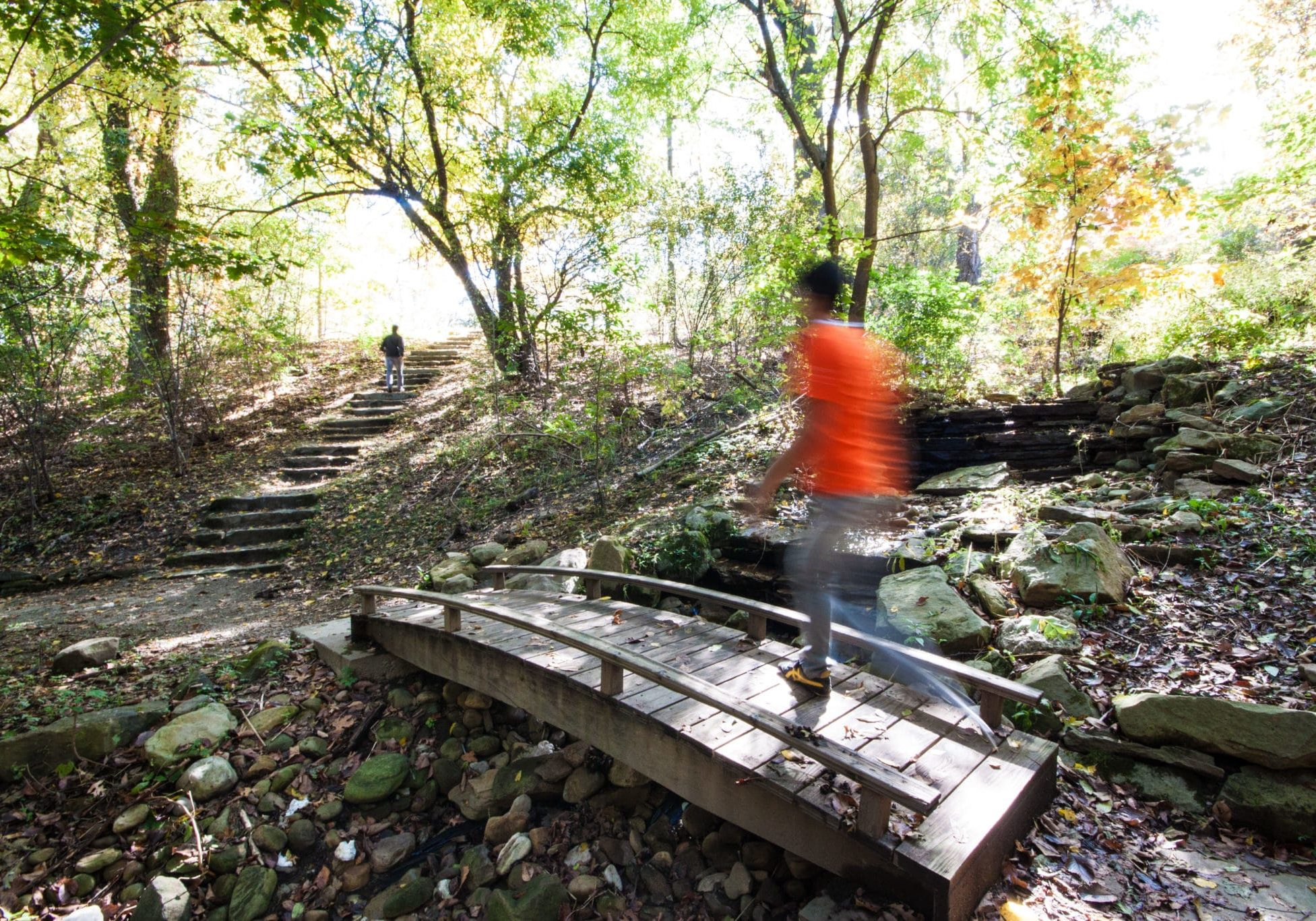 A person walking over small bridge in Highland Park