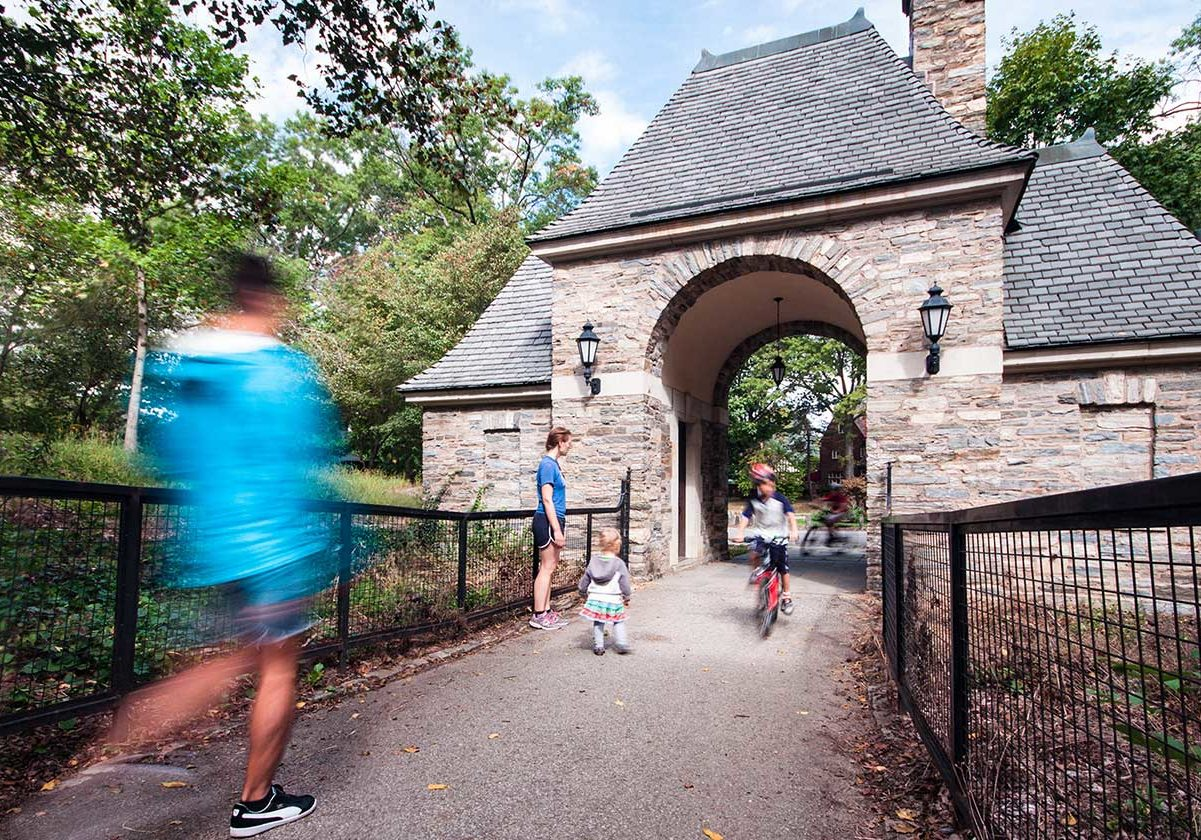 Frick Park's stone gatehouse with people walking and biking through